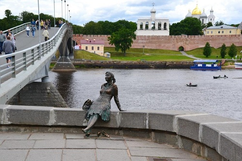 Tired Tourist Girl Monument in Veliky Novgorod. Sculptor Vadim Borovykh. Kremlin Footbridge, Veliky Novgorod, Russia