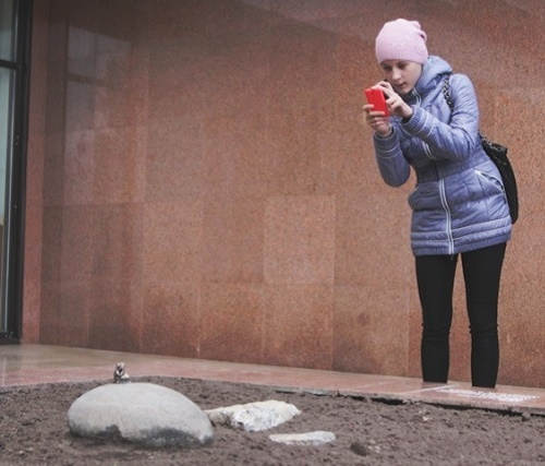 A girl photographing the frog-traveler monument