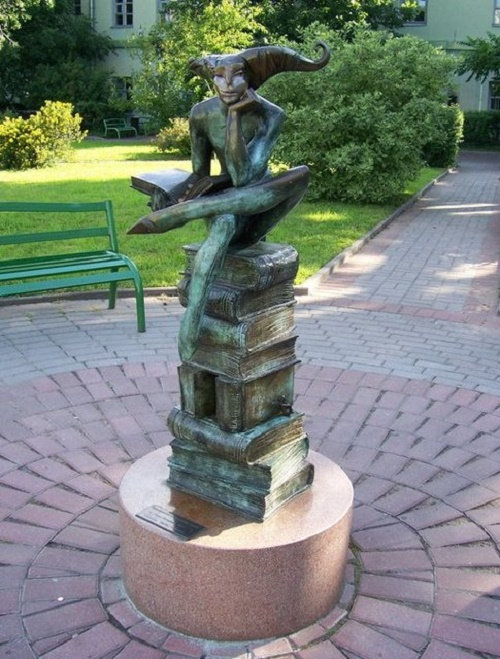 Sculptor Arsen Avetisyan 'Reflection on the Little Prince'. On the pile of books, as on the throne, sits the allegorical image of the philosopher of life - the Jester with a book of Exupery