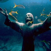 Standing on the floor of the ocean, among fish statue of Jesus