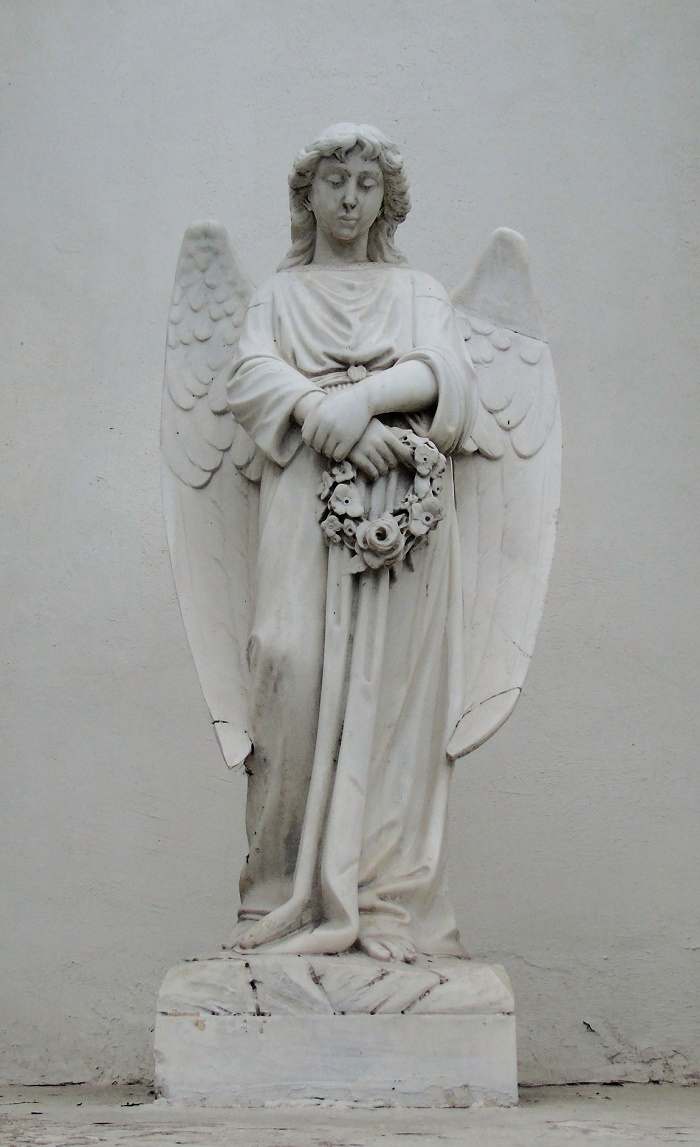 Traditional angel sculpture with a wreath in his hands