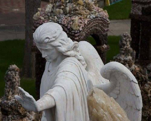 An angel statue. The main entrance on the North side of the Grotto of the Redemption is decorated with the sculpture of archangel