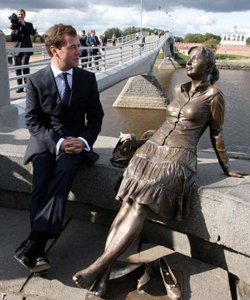 Prime Minister of Russia Dmitry Medvedev next to a monument to a tired tourist girl
