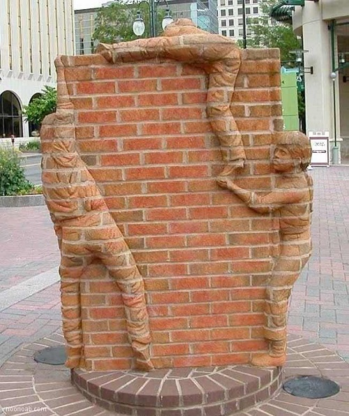 Absolutely brilliant sculptural composition of bricks - boys climbing the wall