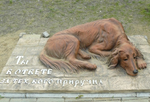 Sad abandoned dog Monuments. The inscription on the pedestal 'You become responsible, forever, for what you have tamed'