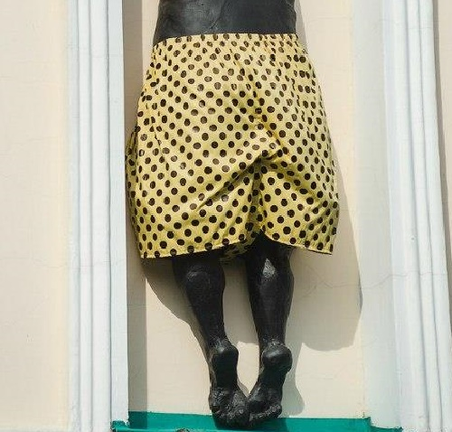 The museum workers carefully change his pants, and currently they are bright yellow Polka dots