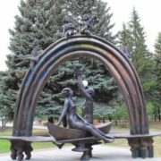 Sculptural composition - a family floating in a boat along the river of life, over which a rainbow shines - cast from bronze, the central avenue of the park of Ulyanovsk