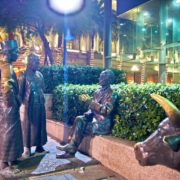 Three men of multicultural Singapore discussing business. River merchants sculpture by Aw Tee Hong on Boat Quay