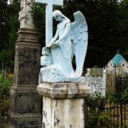 Priest's grave, decorated with a white marble cross and a mournful angel statue