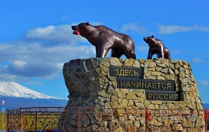 Petropavlovsk-Kamchatsky. A bear with a salmon in her mouth, and behind her - cub