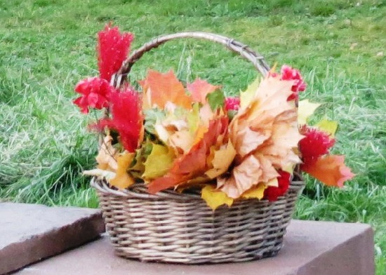 Basket of autumn leaves and flowers on the pedestal